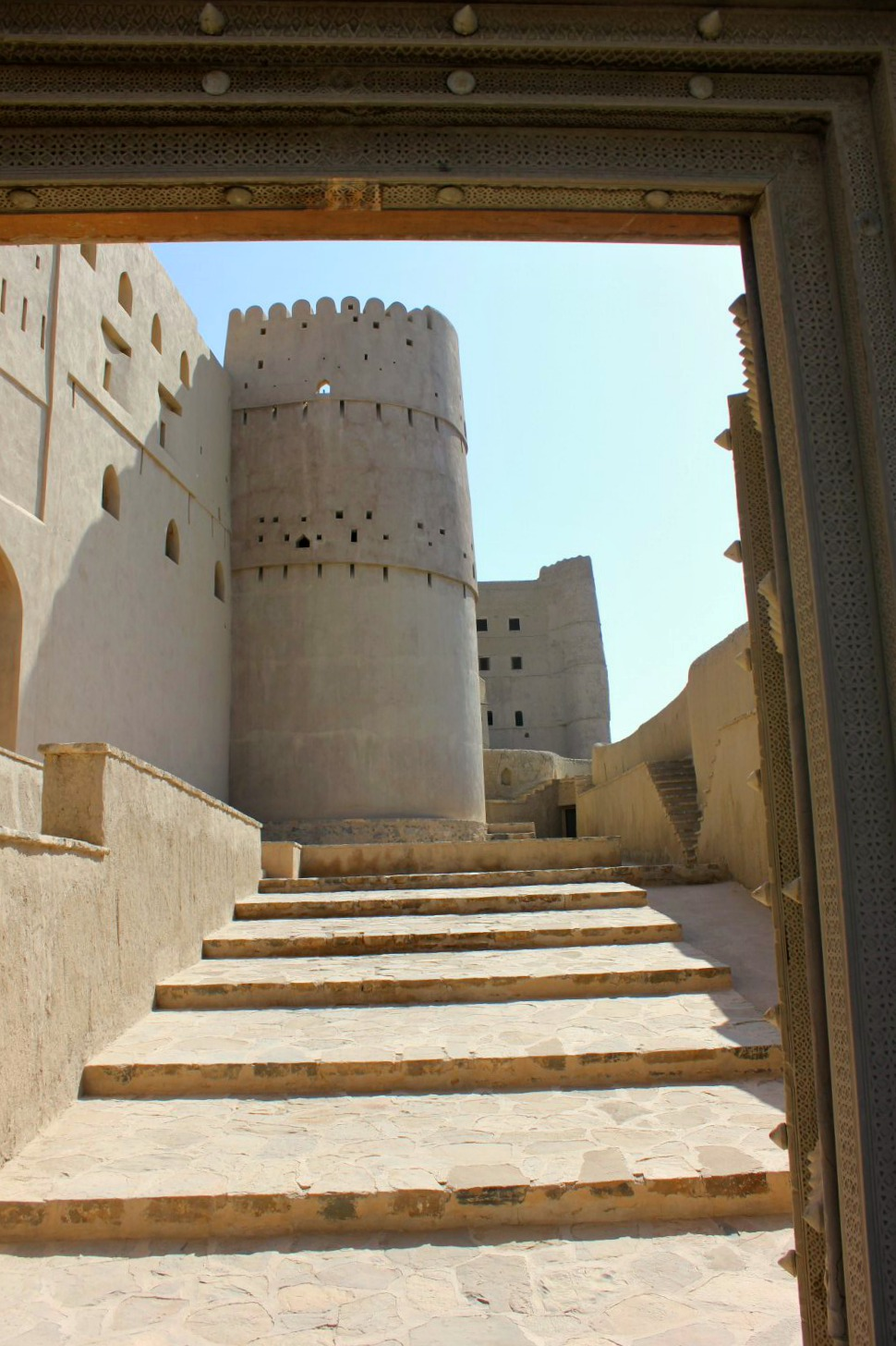A view of the curved white tower at the top of shallow steps in Bahla Fort in Oman - my nine reasons to visit Oman with kids