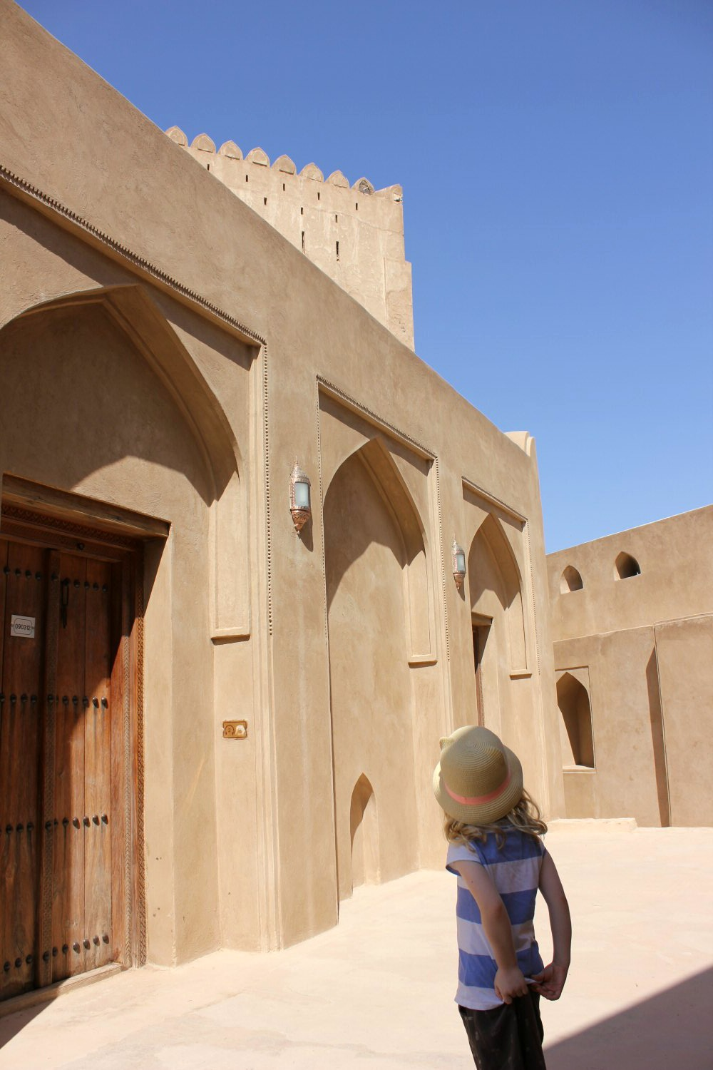 My daughter looks up an arched doorways of the sand coloured buildings in Jarbin Castle in Oman against a blue sky- my nine reasons to visit Oman with kids