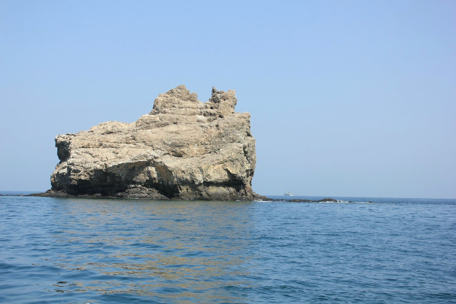A rock in the blue sea off Muscat in Oman - my nine reasons to visit Oman with kids