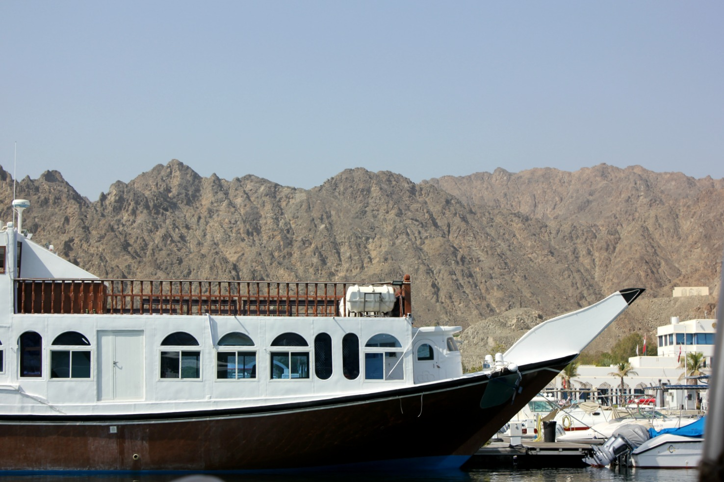 A boat moored at the marina with the mountains in the background - my tips for spending 24 hours in Muscat, Oman with kids