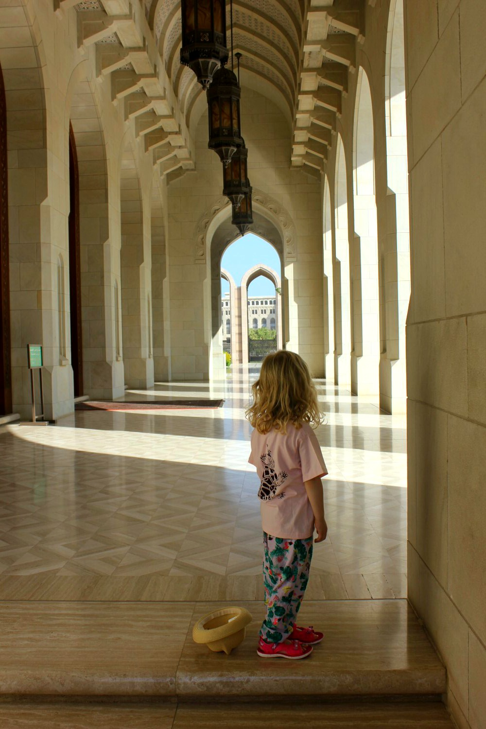 My daughter looks along a covered walkway to the blue sky through an arch at the Sultan Qaboos Grand Mosque in Muscat Oman - the beautiful architecture is one of my nine reasons to visit Oman with kids