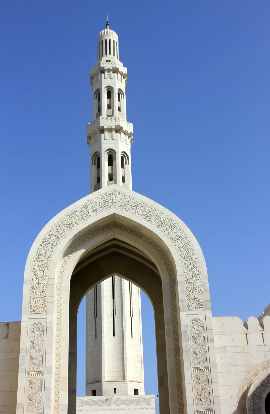 One of the minarets at the Sultan Qaboos Grand Mosque behind a white arch covered with calligraphy in front of a blue sky - my tips for spending 24 hours in Muscat, Oman with kids