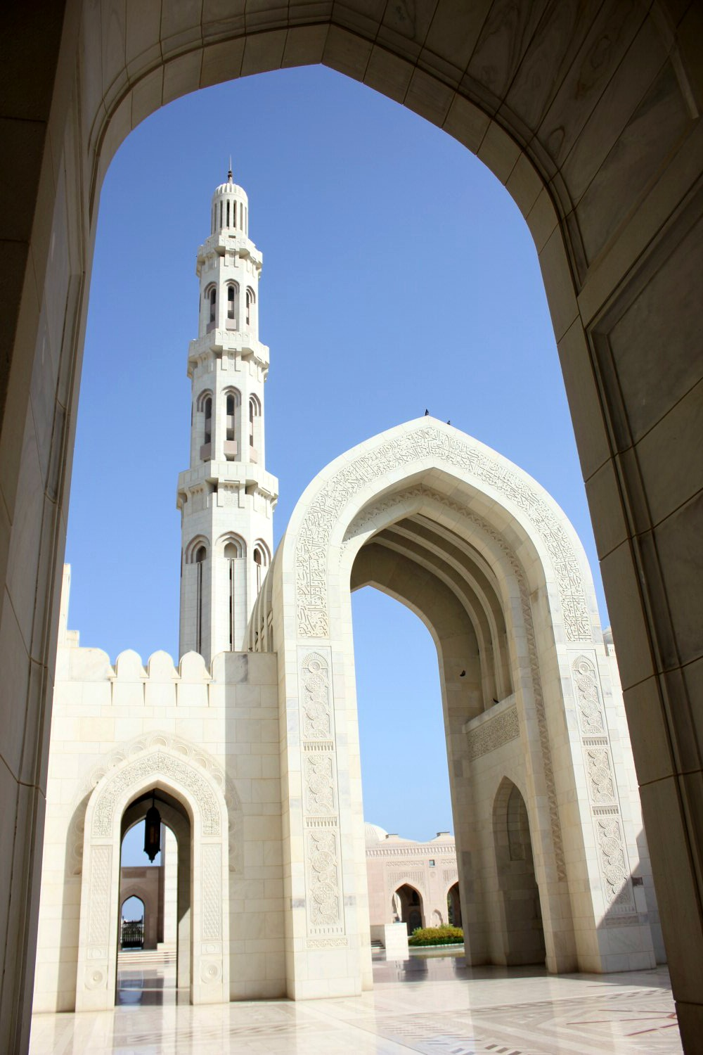 A view of one of the ornate white minarets above an archway at the Sultan Qaboos Grand Mosque in Muscat Oman - the beautiful architecture is one of my nine reasons to visit Oman with kids