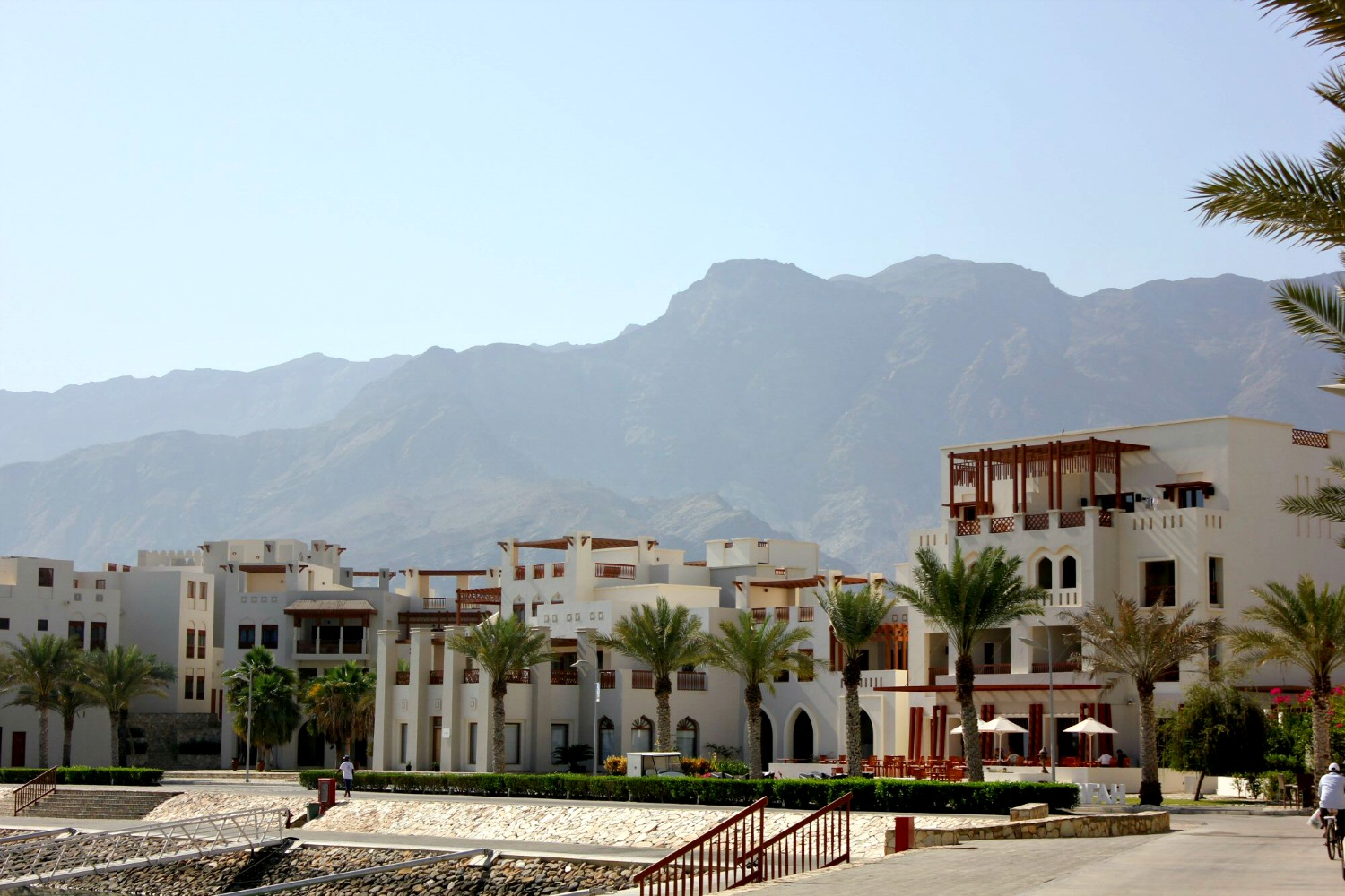 The white buildings at the marina of As Sifa with the mountains behind near Muscat, Oman - my nine reasons to visit Oman with kids
