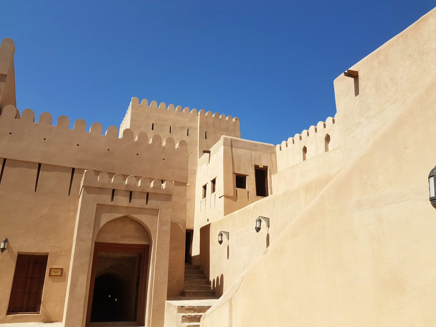A view of the crenelated sand coloured buildings in Nizwa fort in Oman against a blue sky- my nine reasons to visit Oman with kids