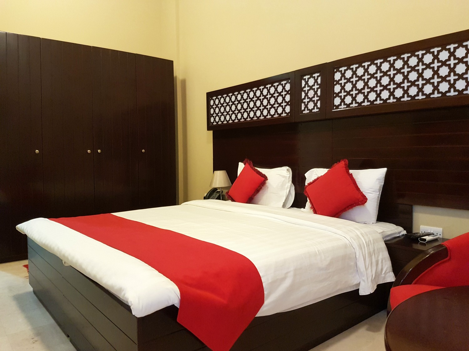 Our bedroom with its sleek dark wood bed and red and white bedcovers - our stay at Ras al Jinz turtle reserve in Oman