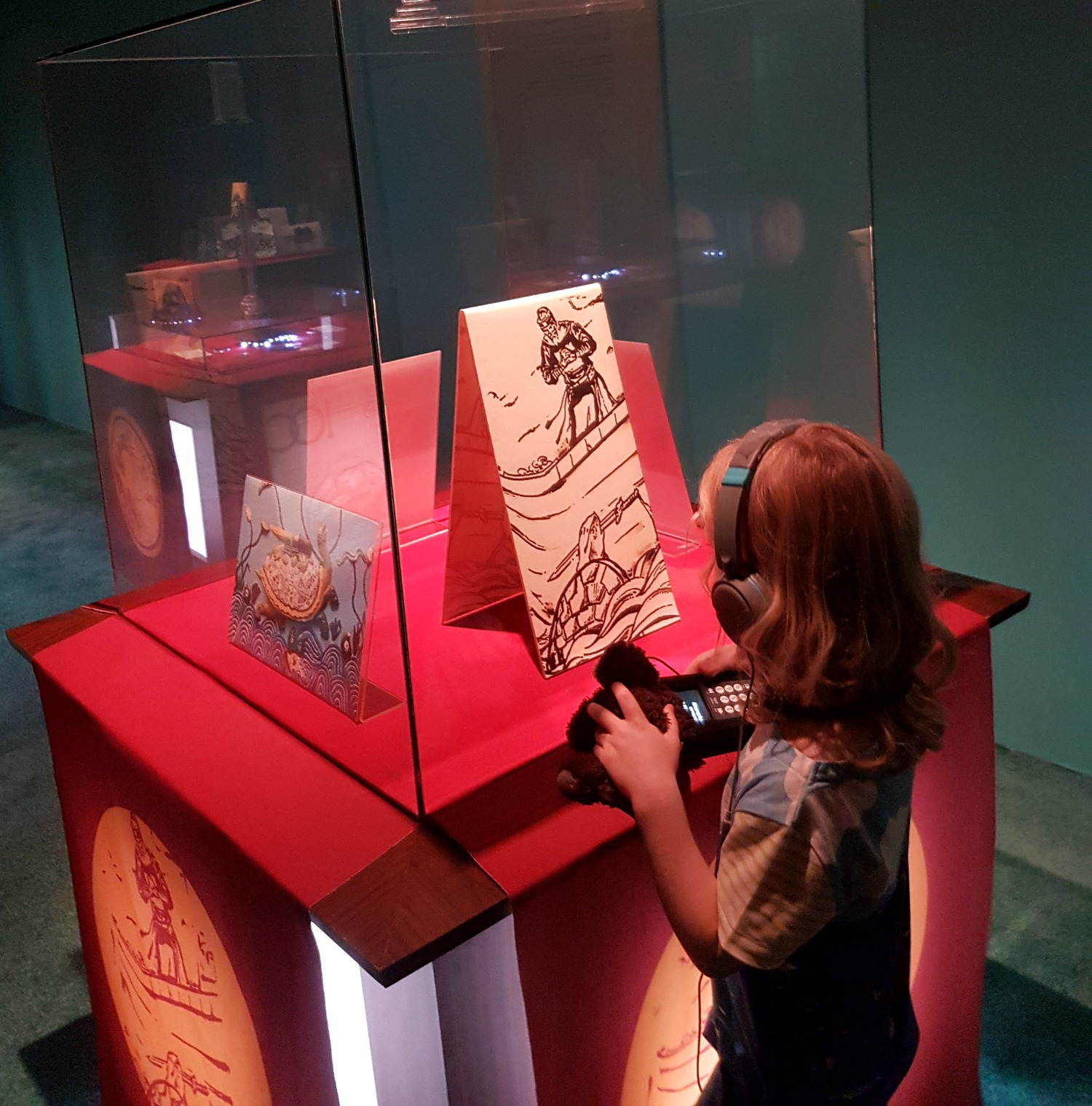 My daughter with audio guide looks at one of the exhibits in a case at the small museum - our stay at Ras al Jinz turtle reserve in Oman