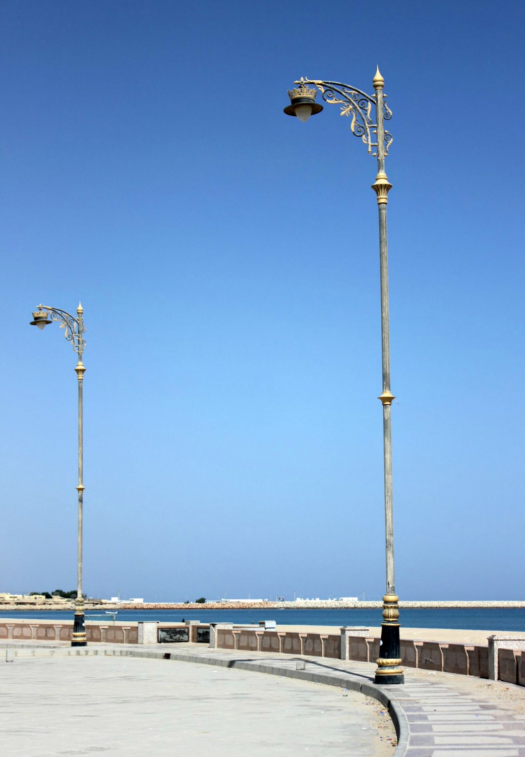 Ornate lampposts against a blue sky on the Corniche at Sur in Oman - my nine reasons to visit Oman with kids