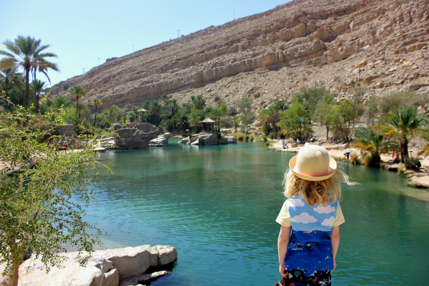 My daughter looks out across the pool to the desert mountains at Wadi Bani Khalid - one of the surprised tucked away in the bone dry peaks, and one of my Oman travel lessons learned