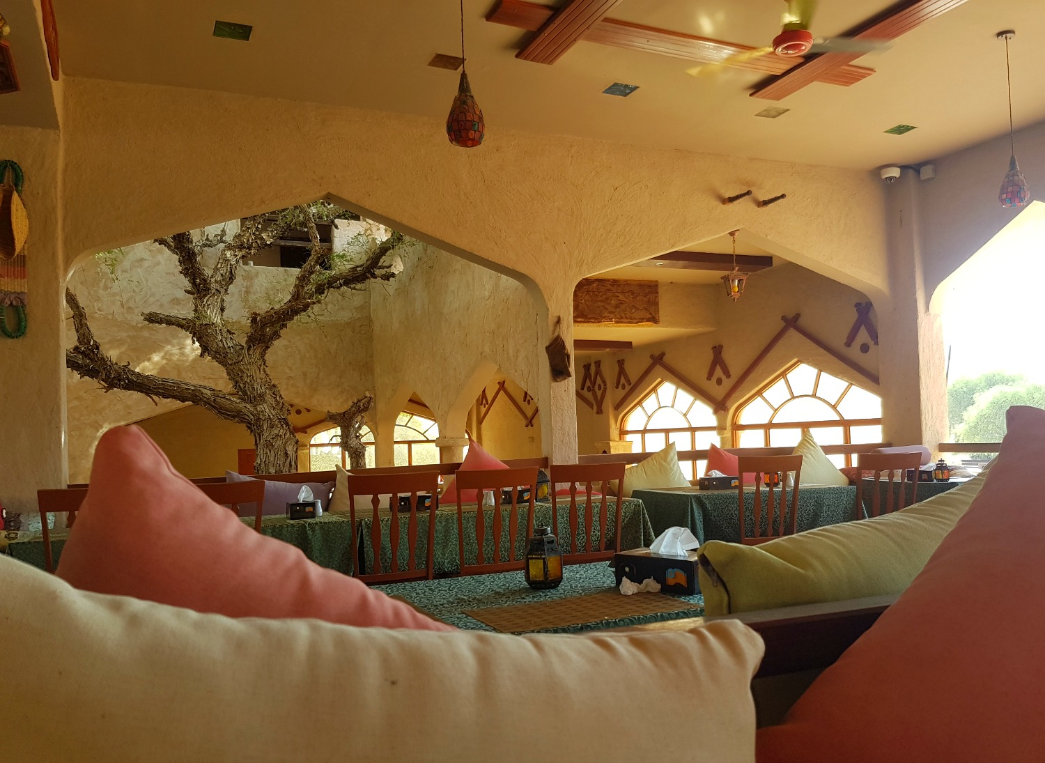 Cushions on the seats at the restaurant and view to the Arabian style windows behind at 1000 Nights Camp - our stay in Wahiba Sands, Oman