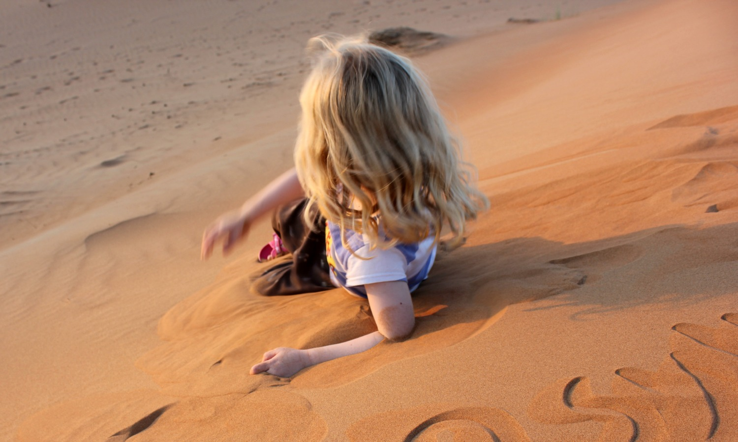 My daughter slides gently down one of the deep orange dunes in Wahiba Sands, Oman at sunset - our stay in Wahiba Sands