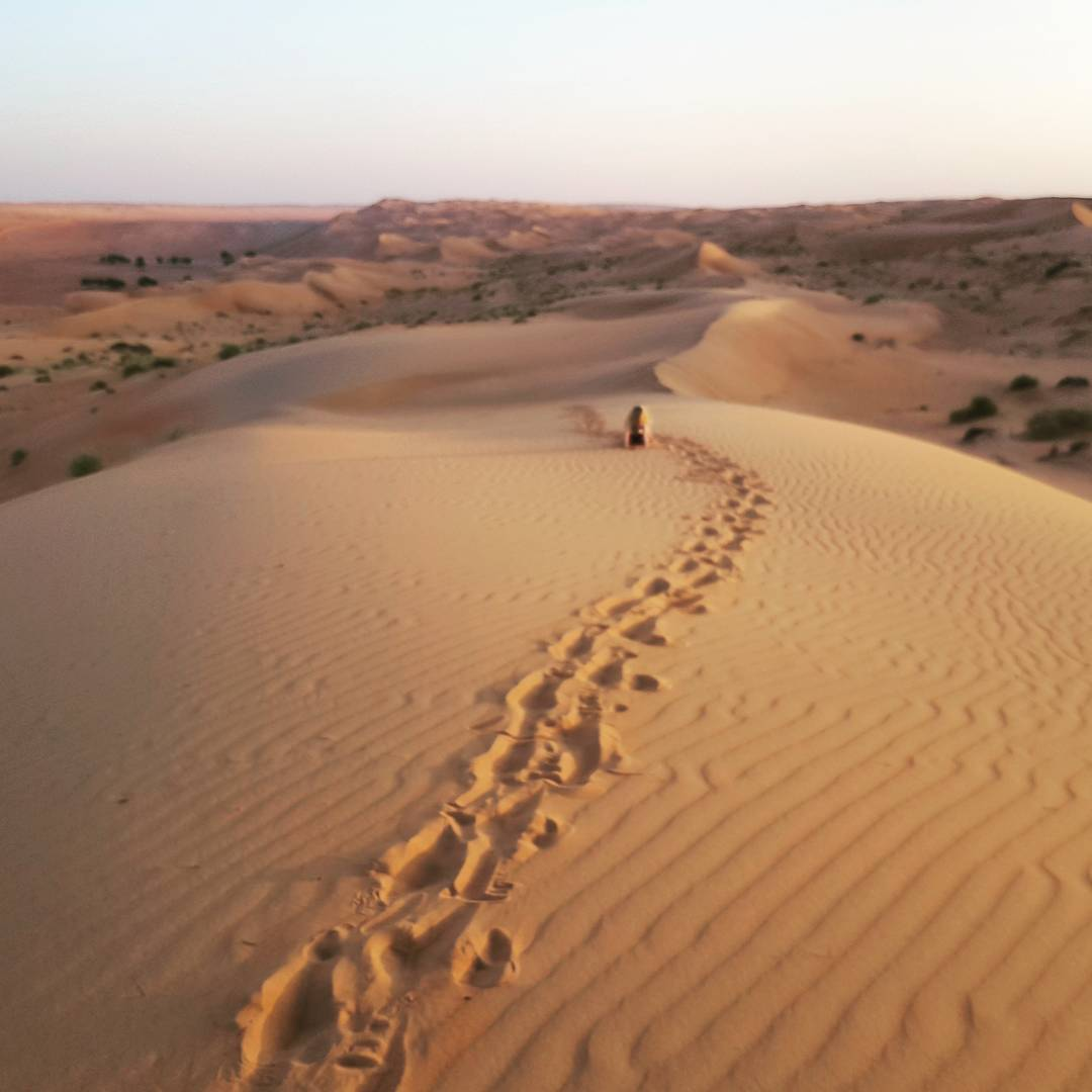 Footprints across a sand dune with my daughter visible in the sand in the distance, at Wahiba Sands in Oman - my nine reasons to visit Oman with kids