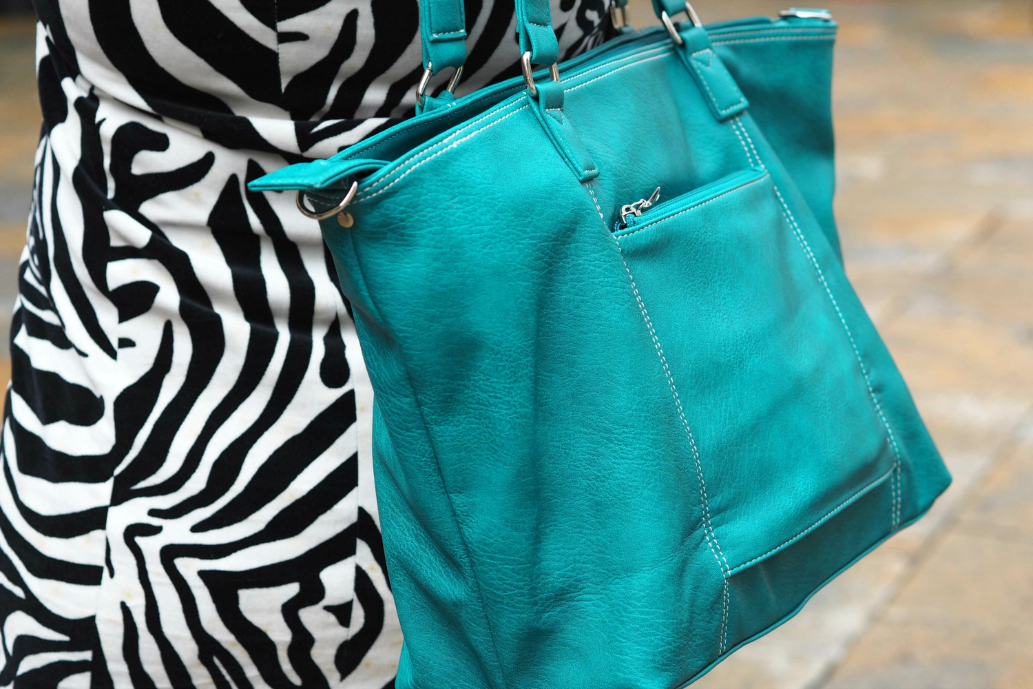 Detail of my zebra print coat, carrying my green Mini Jen bag while exploring in Italy - my Mia Tui hand luggage review