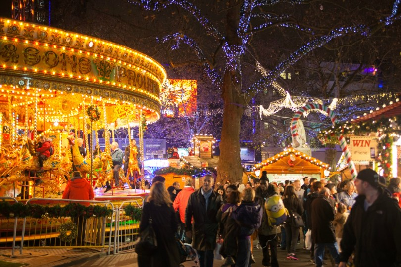 lit up carousel and crowd by the stalls in leicester square the best christmas markets - Best Christmas Markets