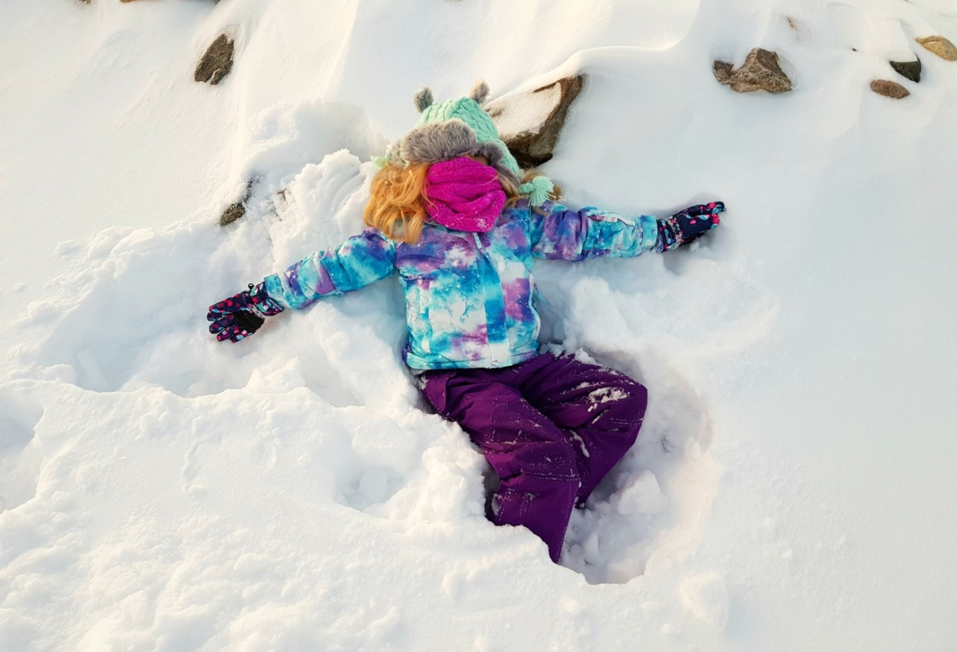 709510c32e5 My daughter lies in the snow, hat pulled down and fleecy snood pulled up  over