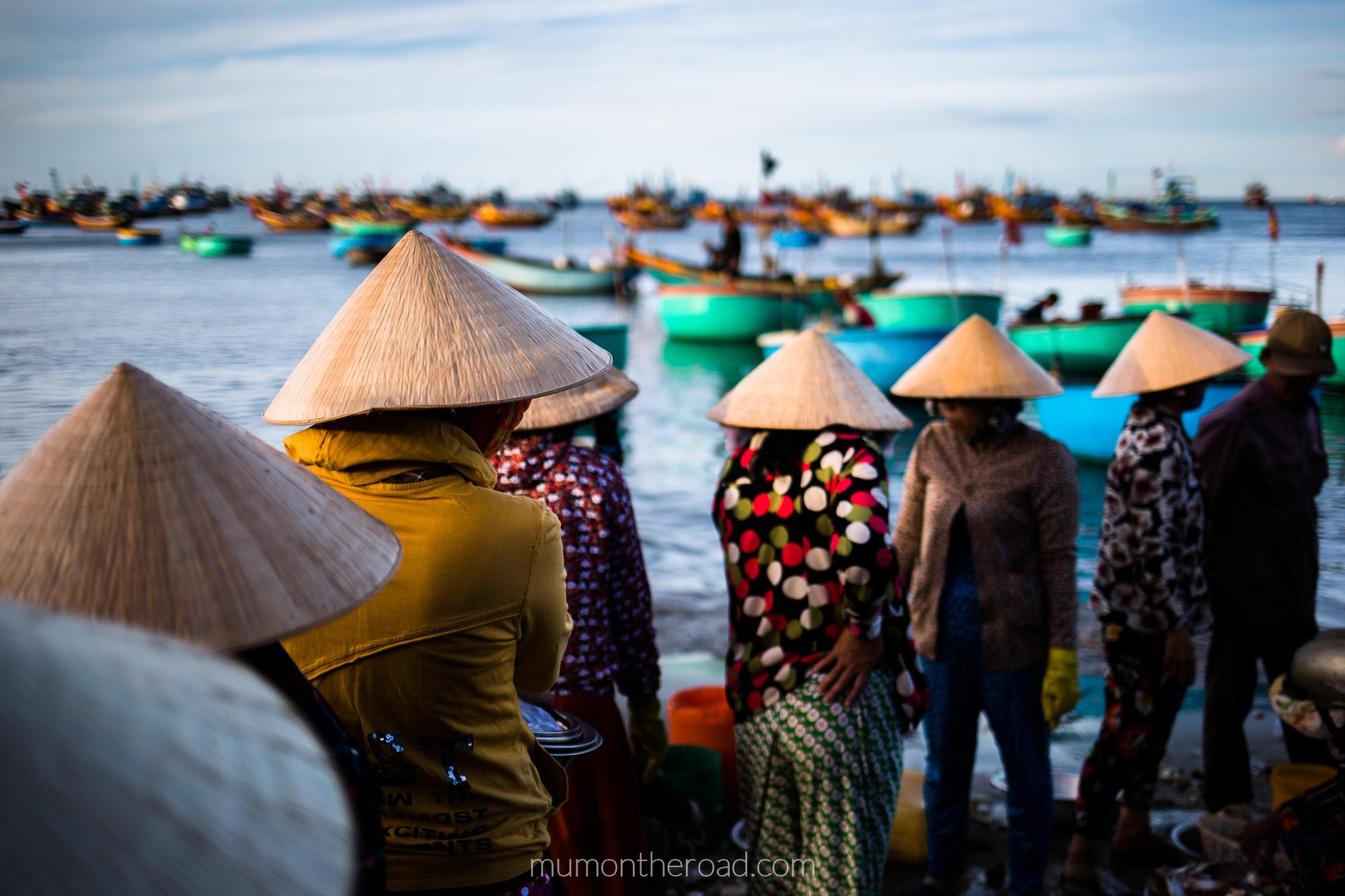 Alignement de vendeuses de poissons portant des chapeaux coniques au village des pêcheurs de Mui Ne au Vietnam