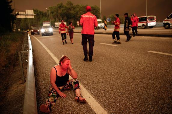 Una mujer superviviente, en estado de shock en la carretera afectada por el voraz incendio. FOTO: AP
