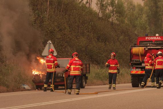 Bomberos, con un coche con el motor incendiado. FOTO: EFE