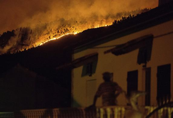 Un hombre en su balcón, con al cortina de llamas al fondo. FOTO:AP