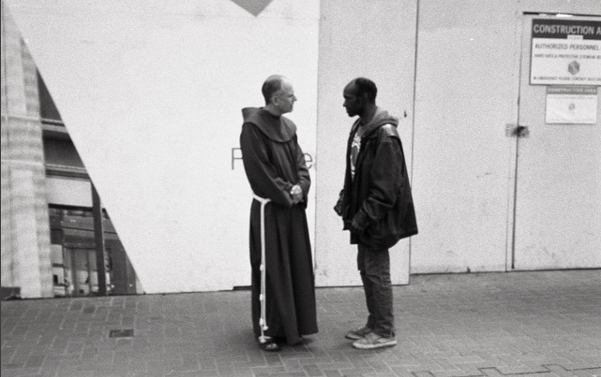 priest on the street by david root