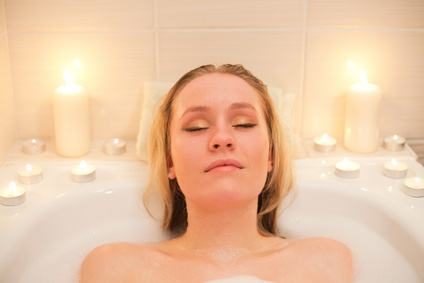 Attractive young blond woman lying in bubble bath with candles (