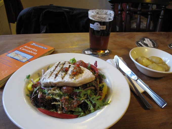 A plate of food and a pint of Butcombe beer stand on a pub table