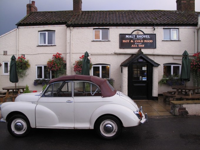 A white Morris Minor car parked outside The Maltshovel pub
