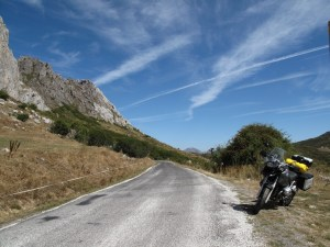 A motorcycle is parked to the side of a small country road which snakes off into hills under a crazy blue sky