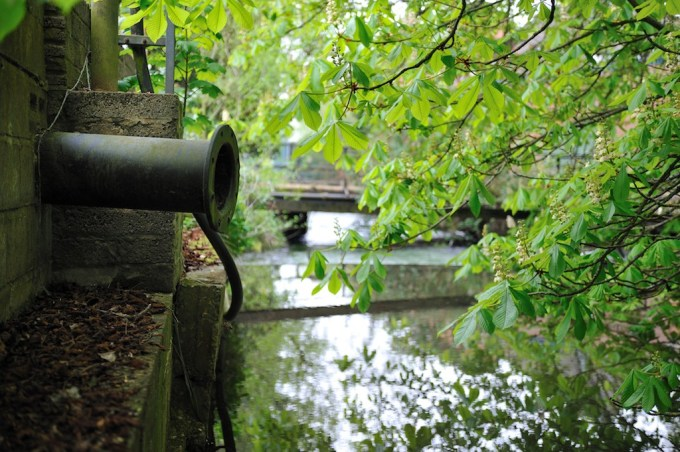 A rusting pipe waits poised above a stream at the edge of Laverstoke Mill
