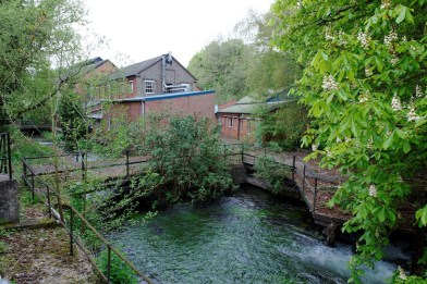 A mill stream runs beneath derelict buildings