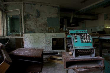 A rusting till sits among the piles of rubble in a dark room