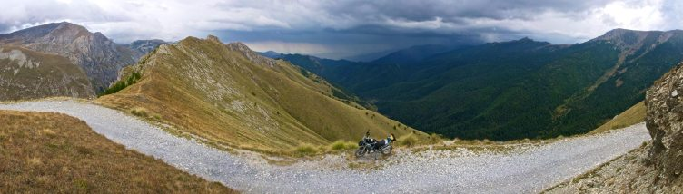 Panorama of bike on a mountain track, thunderstorm in distance