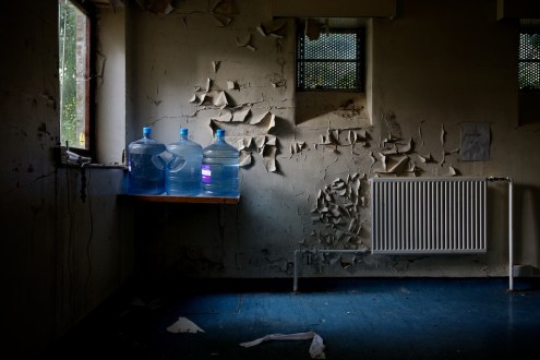 Moody light floods in from a window onto water cooler bottles on a shelf surrounded by peeling paint.