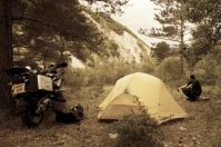 Guy squats by tent and bike, enjoys beer in free campsite