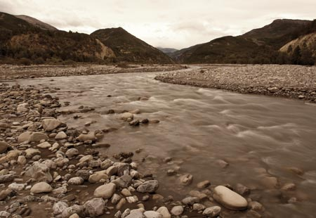 Wide shot of a rock-strewn river with mountains in background
