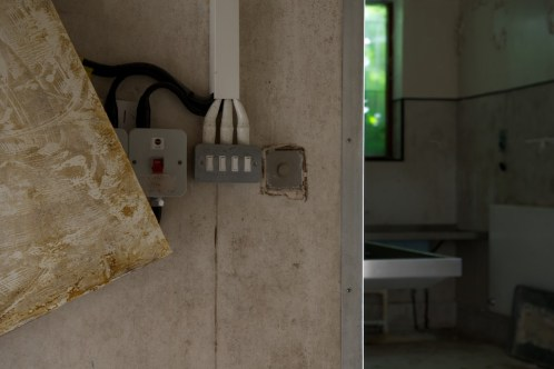 View of wallpaper peeling off wall next to switches, mortuary table just visible in room beyond