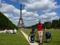 A biker (not sunburnt at all) stands in front of the Eiffel Tower with a blue bike