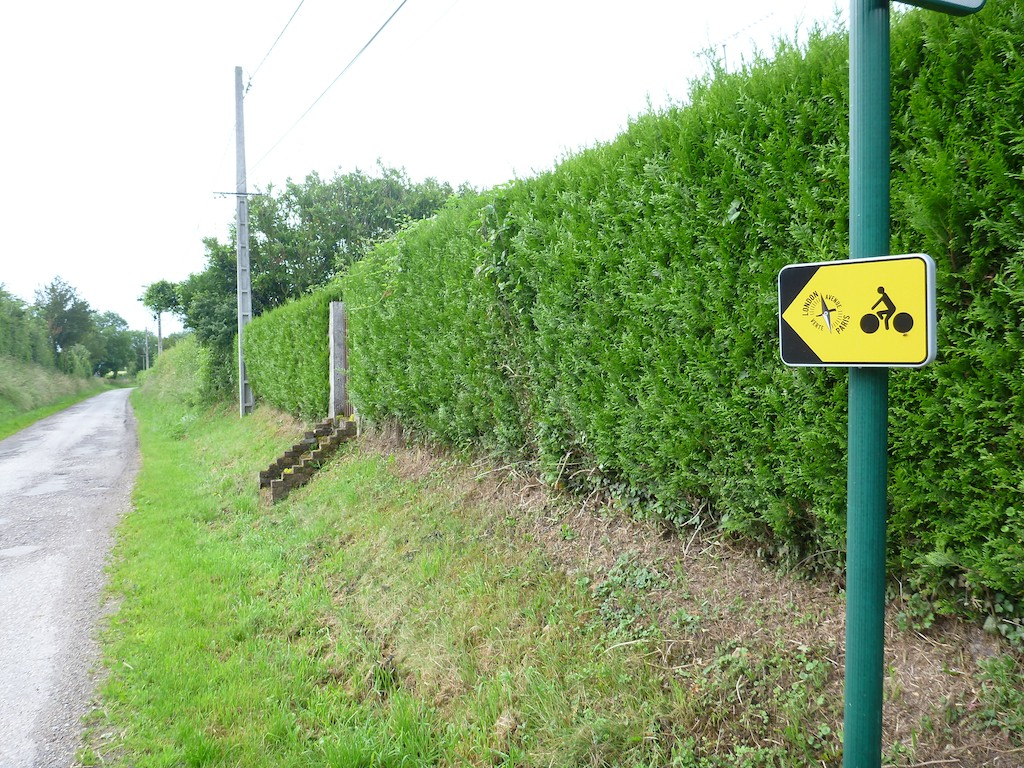 Small yellow marker on a post shows the way to Paris along the Avenue Verte