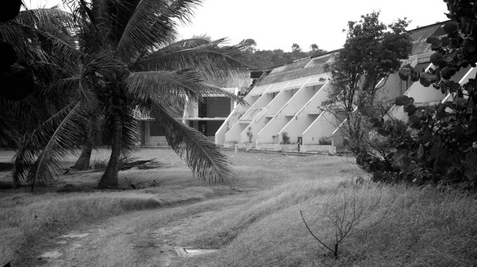 A block of ruined apartments overlooks a grassy courtyard with palm tree
