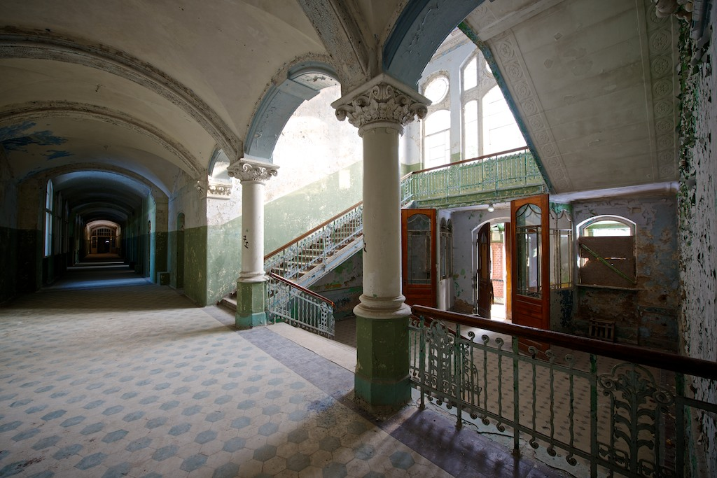 Looking at a grand staircase from the middle floor, long corridor to the left