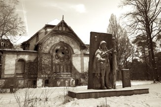 Concrete statue of a Russian soldier stands guard outside a derelict building in the snow