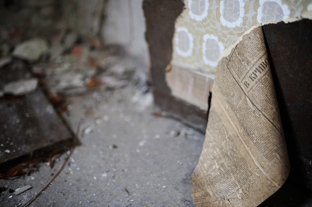 Peeling wallpaper reveals Russian newspaper used as the layer beneath