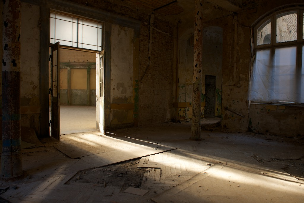 Afternoon sunlight shines in through open doors, casting the otherwise dark room in a golden glow