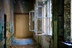 A row of smashed window panes open onto a corridor strewn with rubble