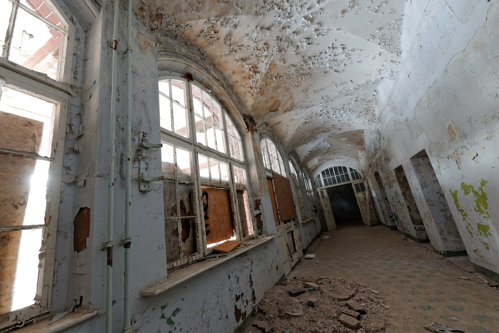 Skewed view of a long corridor with partially boarded windows