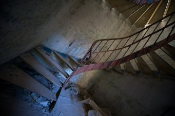 Skewed view of an iron spiral staircase in a dark corner