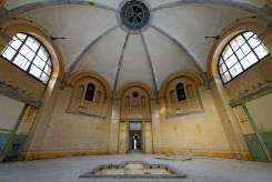 Wide angle view of a vast, domed bathroom lined in beige and white tiles, with a very small tub recessed into the floor