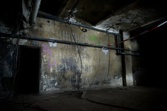 Russian graffiti scratched into the plaster of this torch lit cellar wall