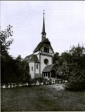 Black and white photo of a church with a very thin steeple