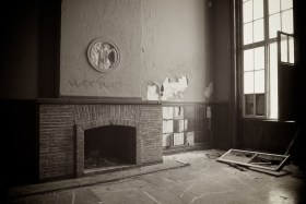 A fireplace next to an open window, Nazi decoration removed from above